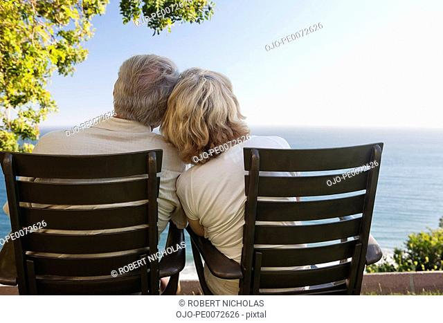 Senior couple in chairs on patio overlooking ocean