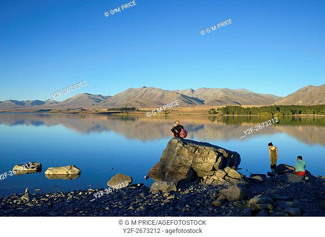 travellers sit by Lake Tekapo, New Zealand