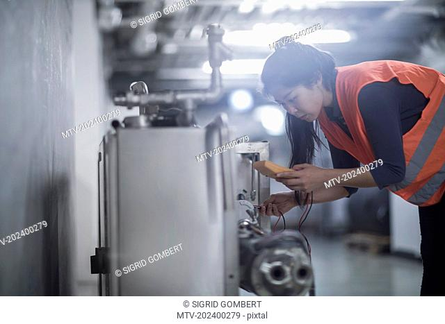 Young female engineer examining machine with multimeter in an industrial plant, Freiburg im Breisgau, Baden-Württemberg, Germany