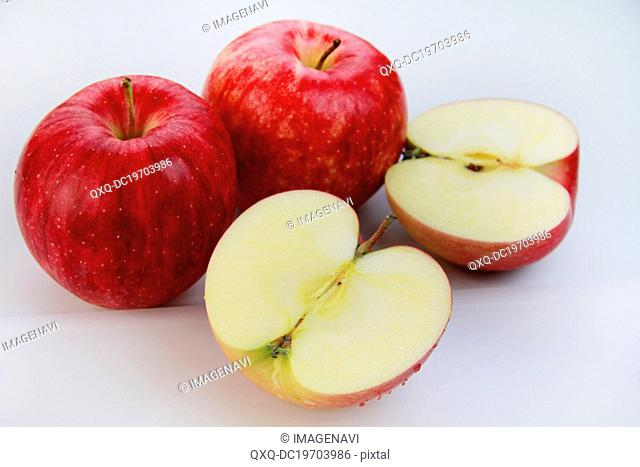 Whole and halved red apples