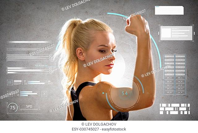 sport, fitness and people concept - young woman posing and showing muscles over gray background