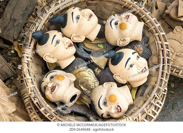 A basket of colorful puppet heads for sale in a market near Mandalay