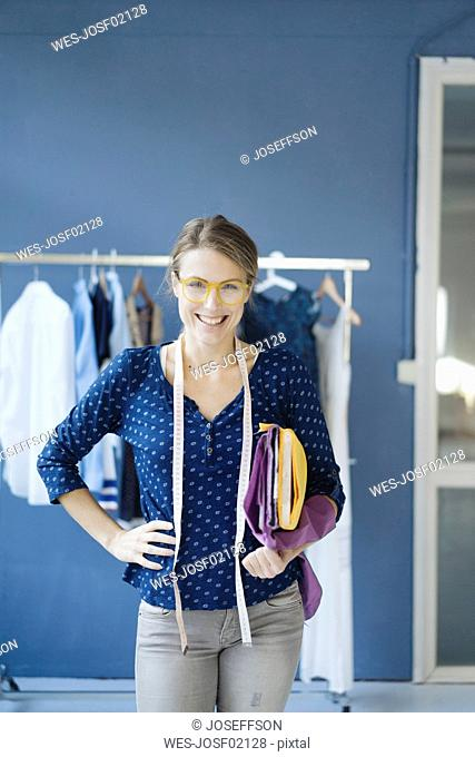 Portrait of laughing fashion designer in her studio