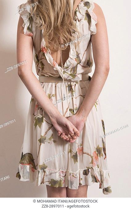 Rear view of a woman wearing a summer dress standing hands her back