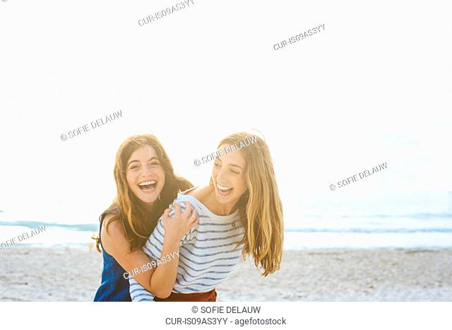 Portrait of two young female friends laughing at coast