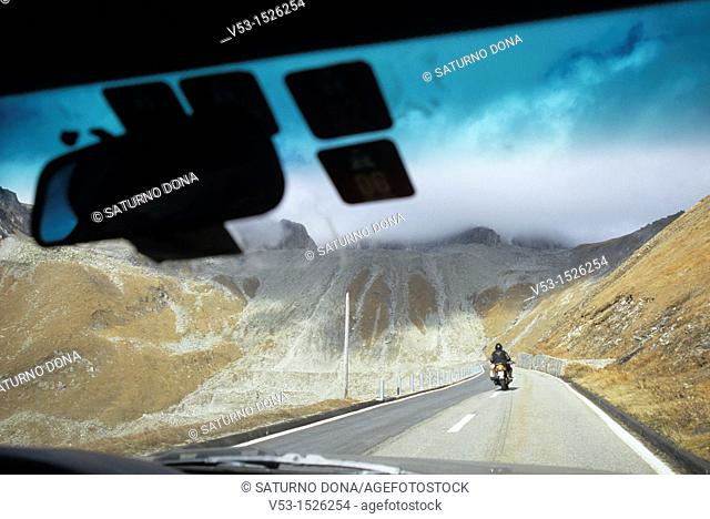 Mountain road and biker through the glass of a car on the Swiss alps, Canton Valais, Switzerland