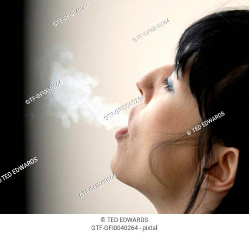 Female blowing cigarette smoke
