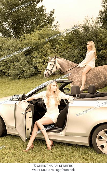 Young woman sitting in cabriolet while teenage girl riding on a horse in the background