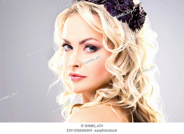 Close-up of absolutely gorgeous model with pure skin and bare shoulders wearing purple flower alike crown over grey background