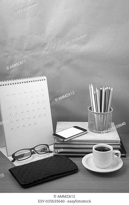 office desk : coffee with phone,wallet,calendar,color pencil box,stack of book,eyeglasses on wood background black and white color