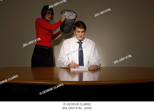 young businesswoman emptying wastebasket over her colleague