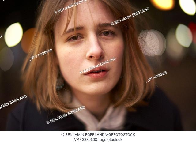 closeup of emotional woman at night in Berlin, Germany