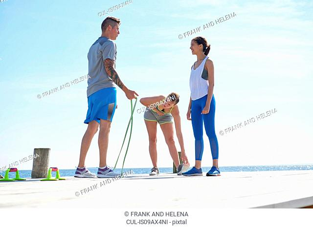 Friends wearing sports clothes on pier with skipping rope