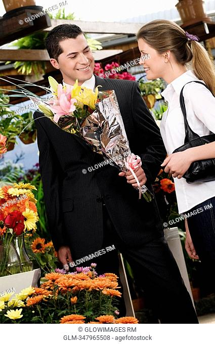 Man holding a bouquet of flowers with a woman smiling at him