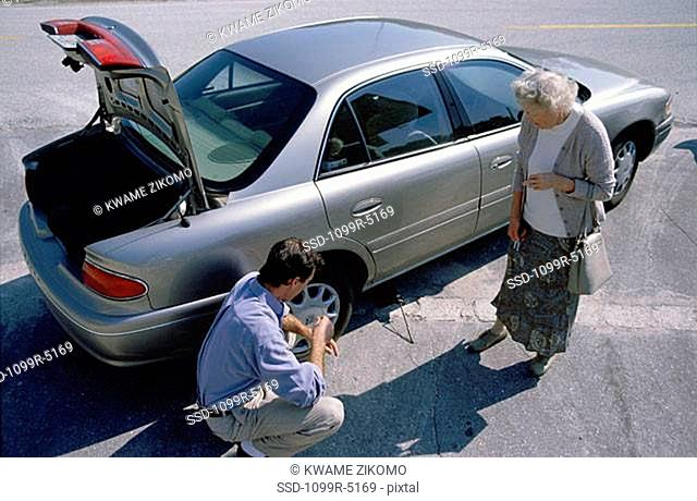 Mid adult man helping a senior woman change a flat tire on her car