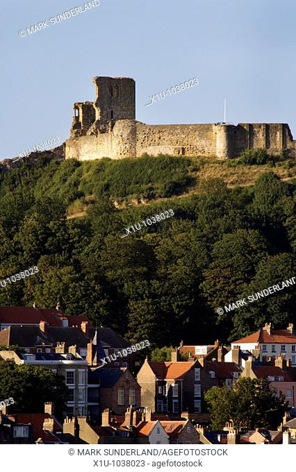The Ruin of Scarborough Castle Looms Over The Town at Sunset Scarborough North Yorkshire England