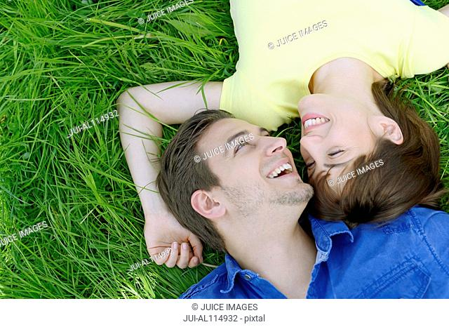 Young couple lying on back on grass