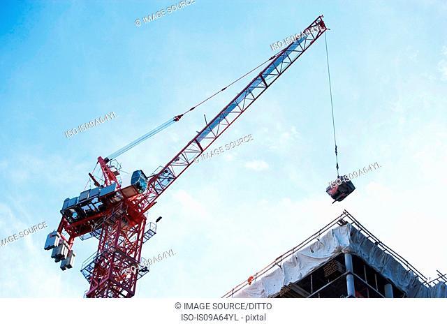 Crane loading equipment on building