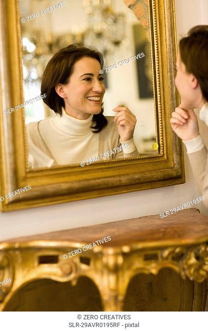 Woman looking into mirror