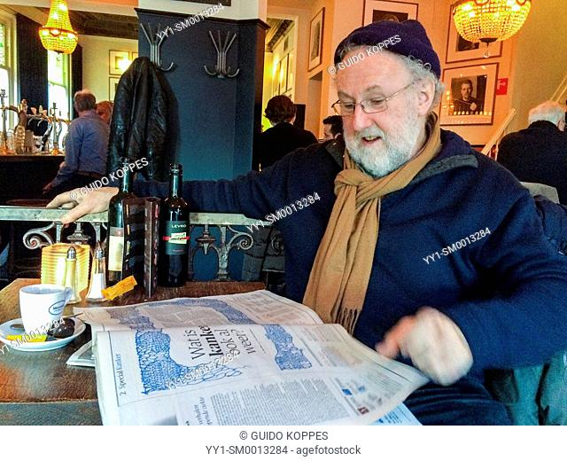 Tilburg, Netherlands. Elder man with knitted hat, glasses and beard reading a newspaper in a cafe, while drinking a cup of coffee