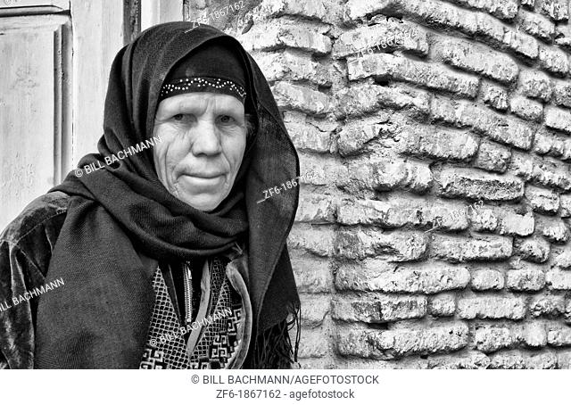 Local Arab woman in veil against sand wall in Tuzeur in Sahara area of Tunisia in Africa
