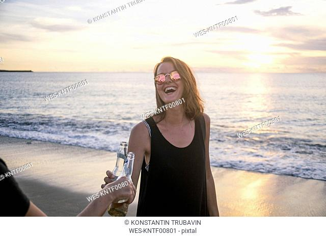 Indonesia, Bali, happy woman clinking beer bottle with friend on the beach at sunset