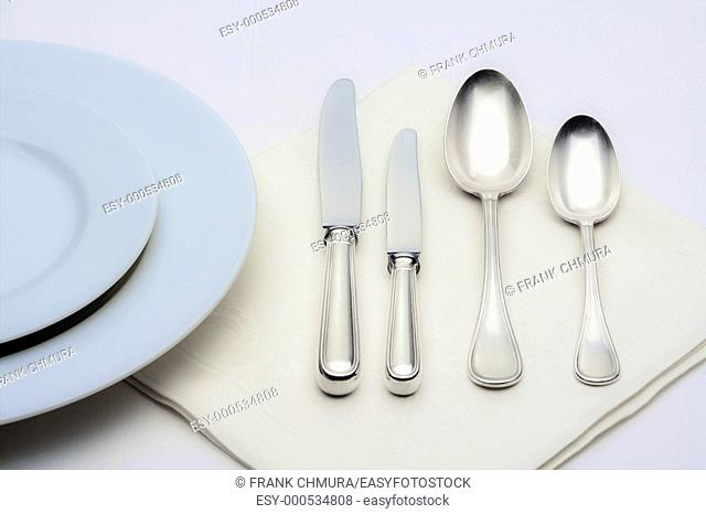 elegant table setting with silverware on white cloth
