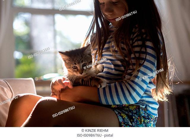 Girl with kitten sitting on lap