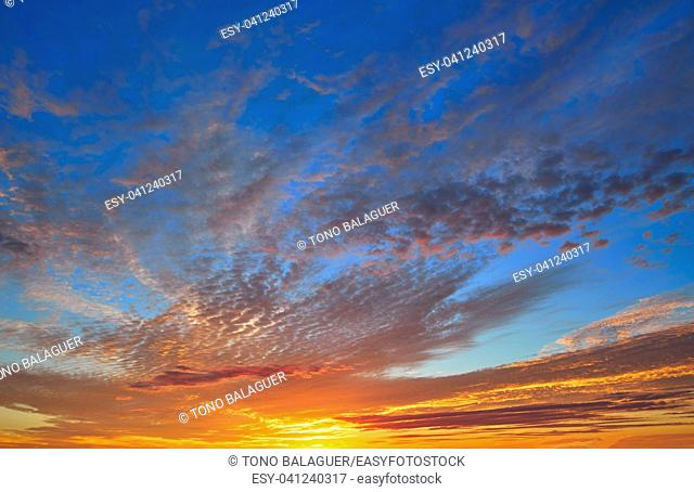 Sunset sky with orange clouds over blue background