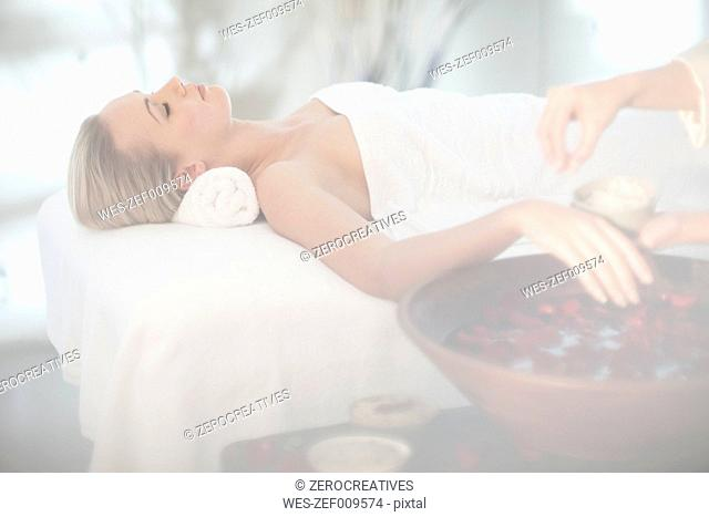 Young woman lying on massage table dipping her hand in rosewater