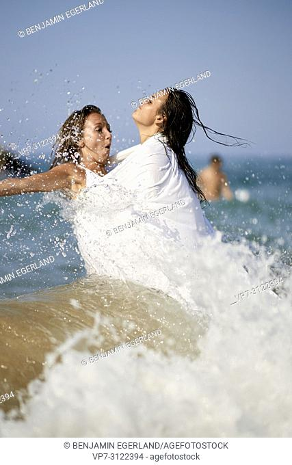 water splashes, waves, two women shrouded in white blanket sheet, standing in sea, best friends, togetherness, vacations. Chersonissos, Crete, Greece