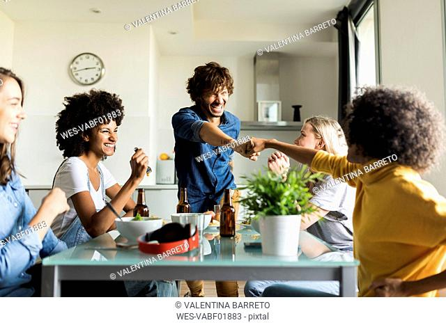 Cheerful friends sitting at dining table