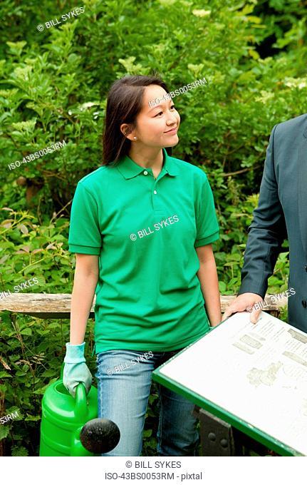 Gardener with businessman in park