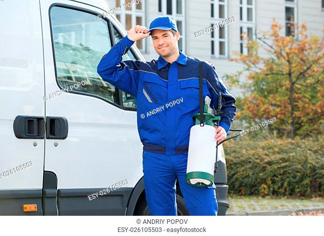 Portrait of happy pest control worker wearing cap while standing against truck