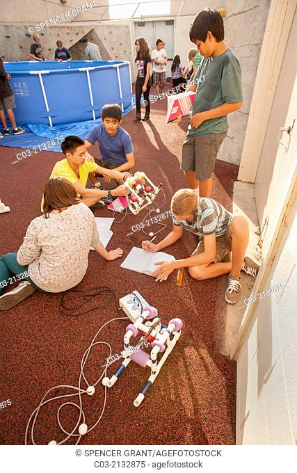 Multiracial middle school students in Mission Viejo, CA, refer to notes and test the remote operated submarine vehicles (ROV) they built in their robotics...