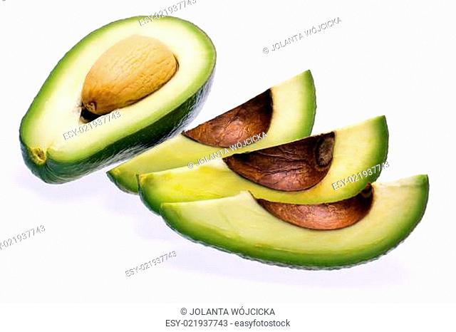 pieces of cut fresh avocado with stone isolated on white background