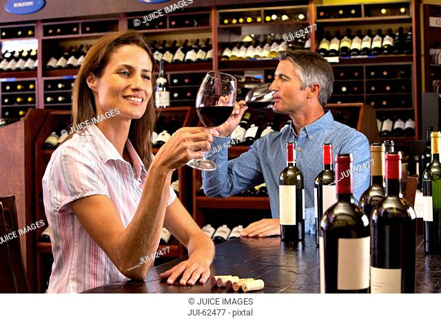 Curious couple examining glasses of red wine in wine shop