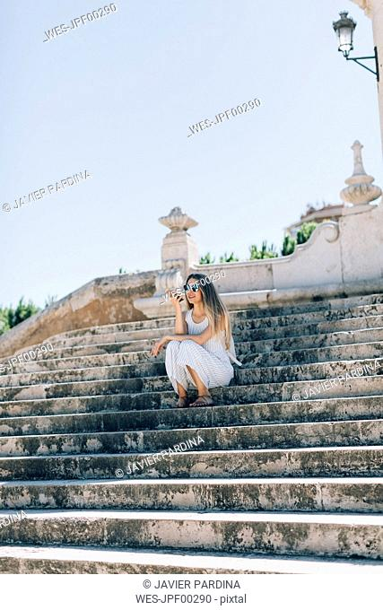 Spain, Valencia, woman sitting on stairs using smartphone