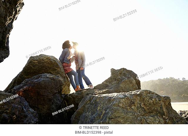 Couple kissing on boulder on beach