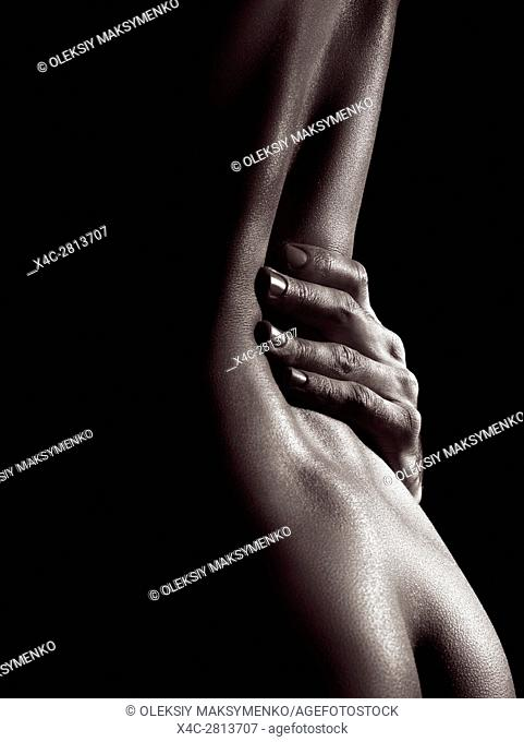 Sensual erotic closeup of a sexy nude woman body with man hand on her waist, black and white body parts abstract fine art