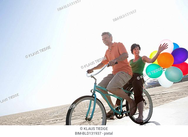 Caucasian couple riding bicycle by beach