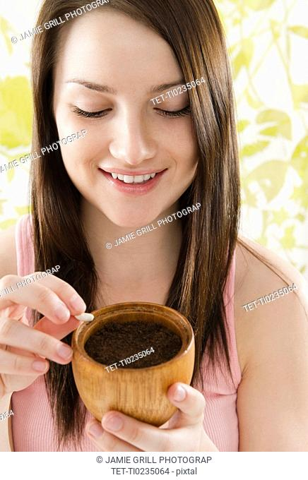 Smiling young woman holding pot with soil and bean