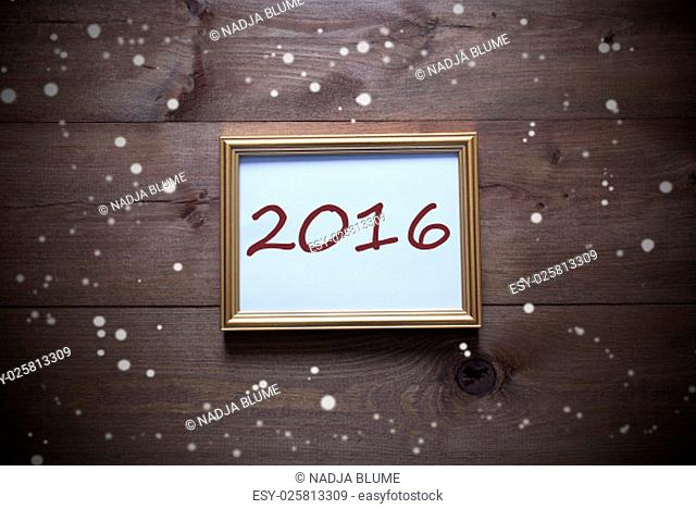 One Golden Picture Frame On Wooden Background. English Text 2016 For Happy New Year. Rutic Vintage Or Retro Style. Snowflakes For Christmas Or Winter Atmosphere