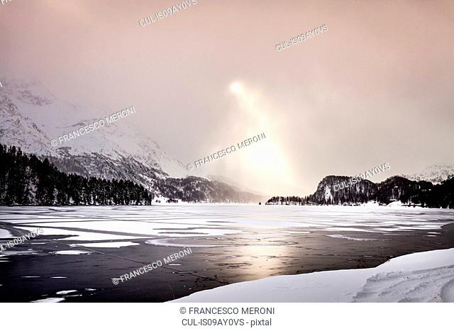 Sunbeams shining on frozen lake and snow covered mountains, Engadin, Switzerland