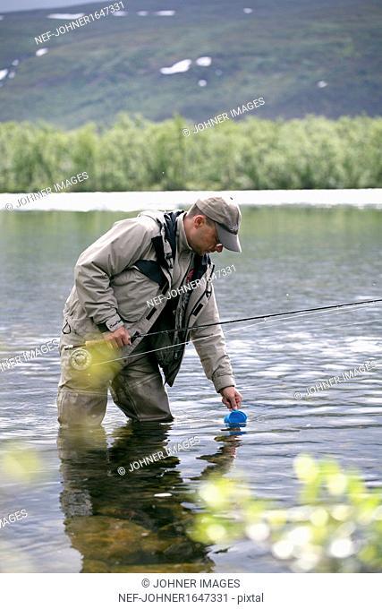 Man fishing in mountain lake