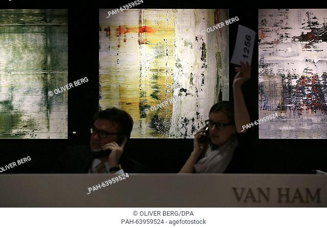 Employees at the Van Ham auction house accept bids per phone in front of paintings by the artist Gerhard Richter in Cologne,Germany, 26 November 2015