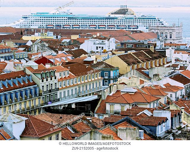 Cityscape of central Lisbon with giant cruise ship Oceana docking on the waterfront. Seen from viewing platform at top of Elevador de santa Justa, Portugal