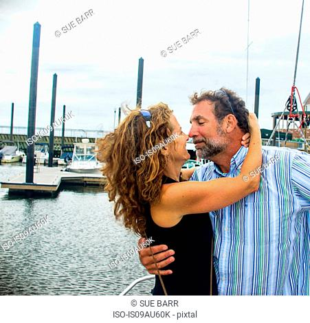 Mature couple in marina nose to nose smiling