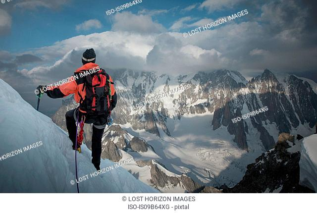 Mountain climber on side of mountain, looking at view, Montblanc, Languedoc-Roussillon, France, Europe
