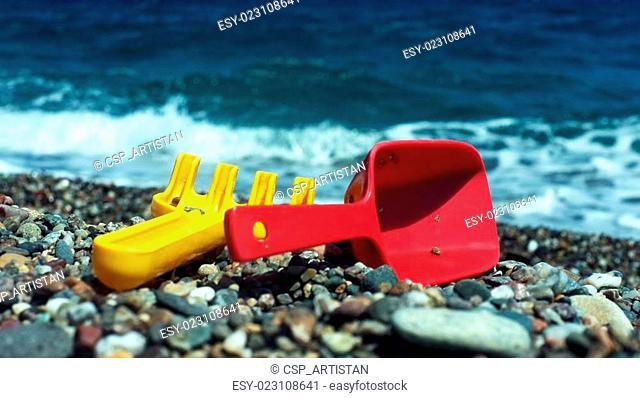 Child's rake and shovel on a beach